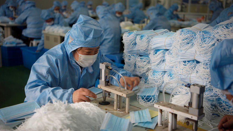 Employees work on a production line for surgical masks at a factory, following an outbreak of the novel coronavirus in the country, in Nantong, Jiangsu province, China