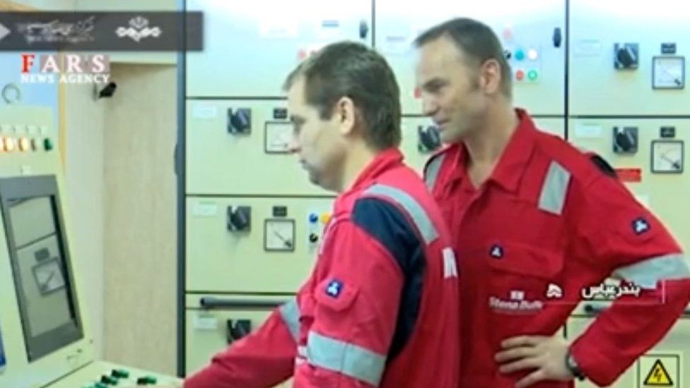 Crew members monitor computers onboard the tanker