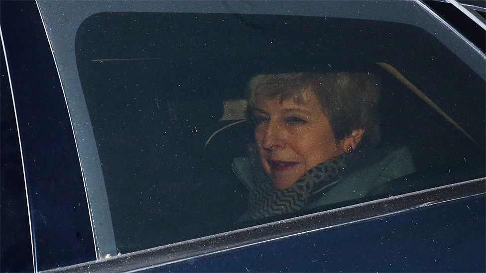 Theresa May seen leaving Parliament through a car window on 27 March