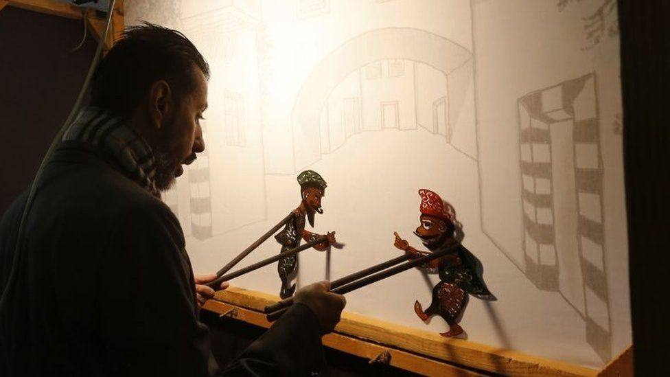 Syrian last shadow puppeteer Shadi al-Hallaq is seen moving his puppets Karakoz (R) and Eiwaz (L) from inside his booth during a presentation in Damascus on 3 December 2018. -