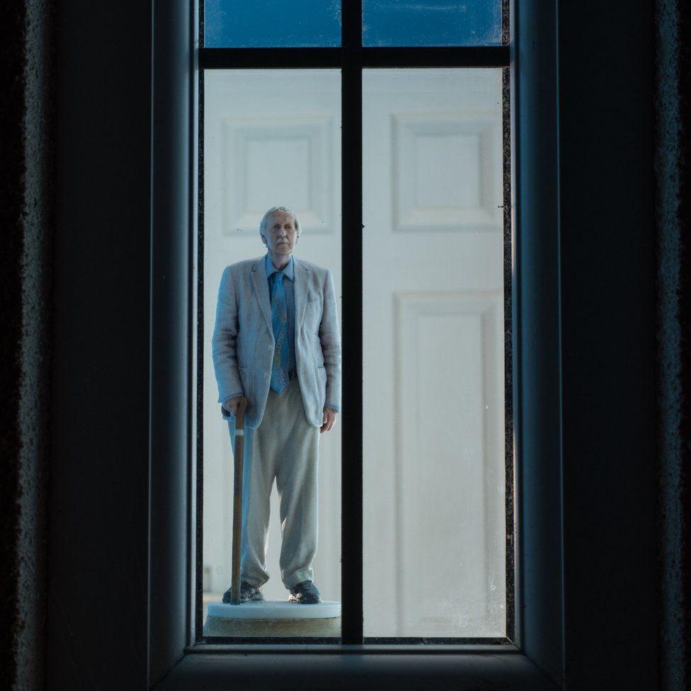 A man stands looking out of a window