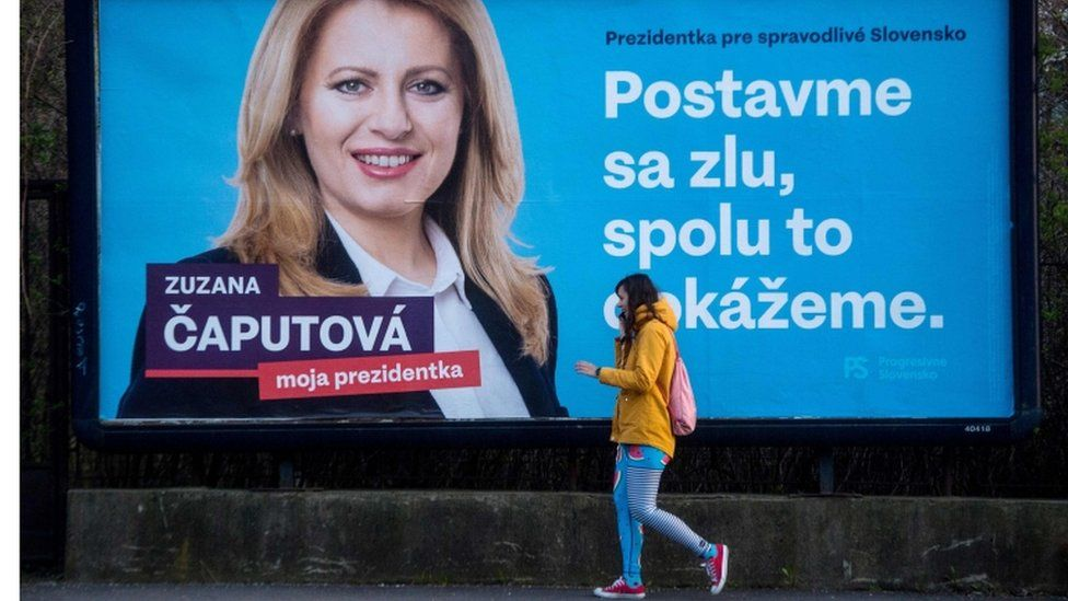 """A girl walks past one of Ms Caputova's campaign posters, which reads """"Stand up against evil, together we can do it"""""""