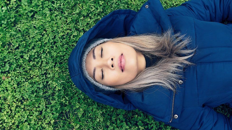 Young woman in a blue coat sleeping on a meadow
