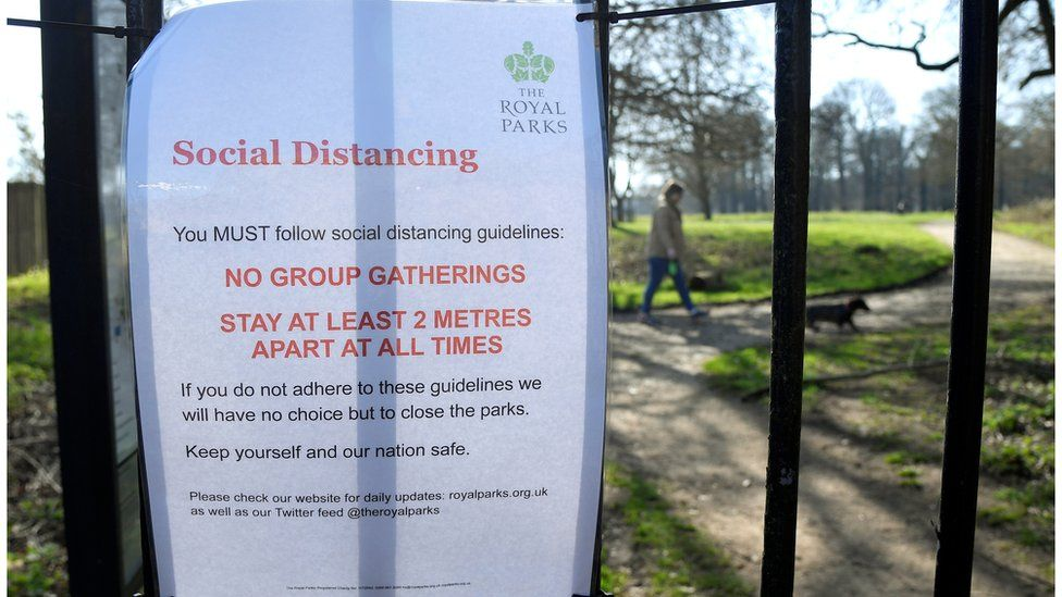 A sign issued by the Royal Parks advising on social distancing at an entrance to Richmond Park