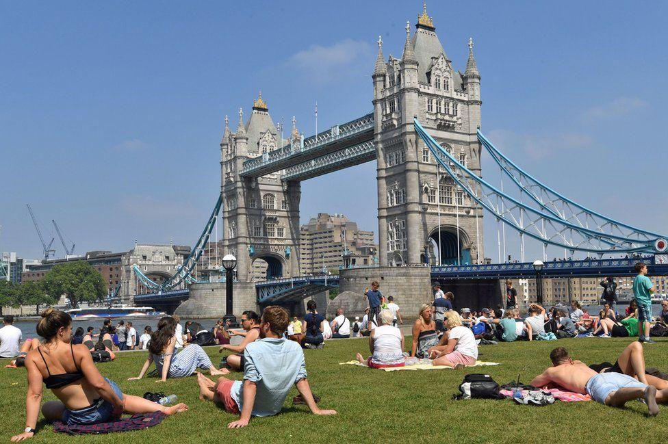 People in sun next to Tower Bridge