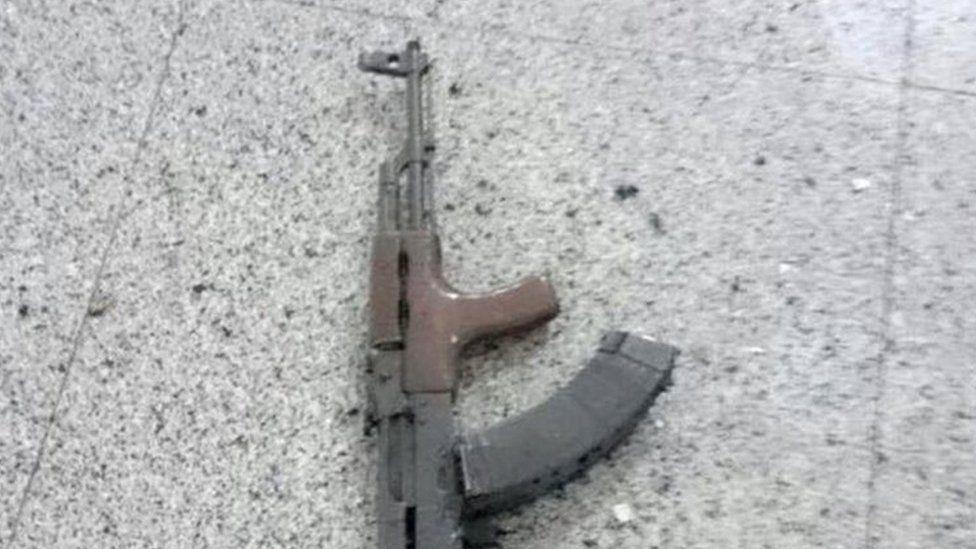 A Kalashnikov assault rifle is seen on the floor at Ataturk airport