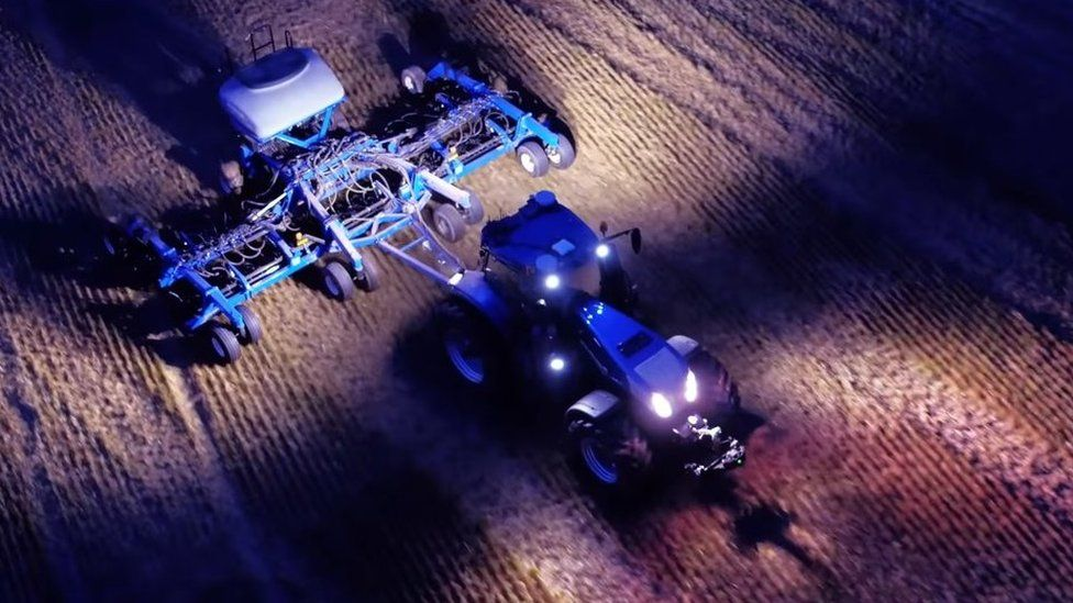 Tractor working a field at night