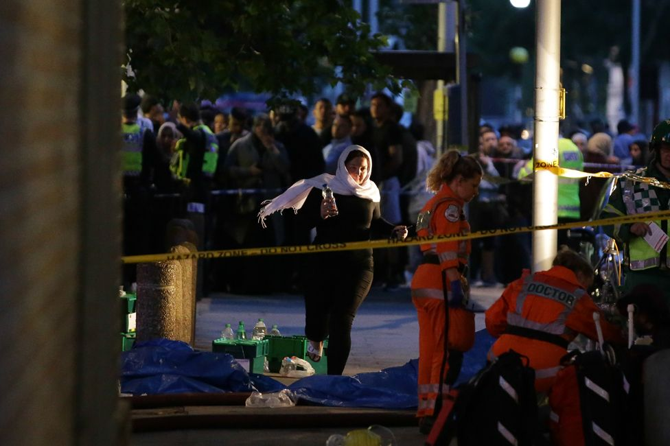 Paramedics, police and crowds of people outside Grenfell Tower