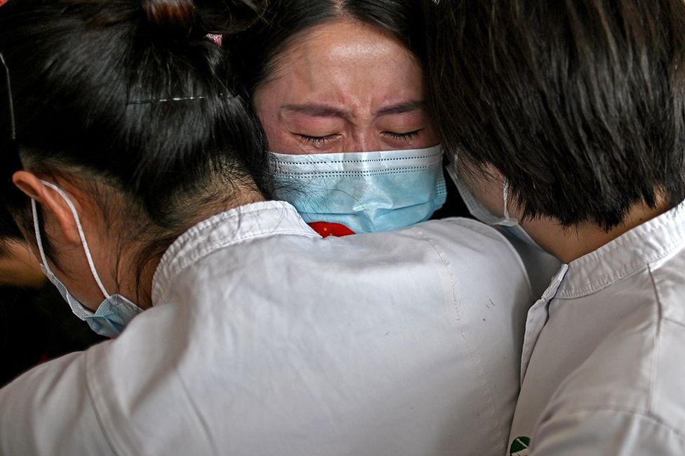 Medical staff hug nurses