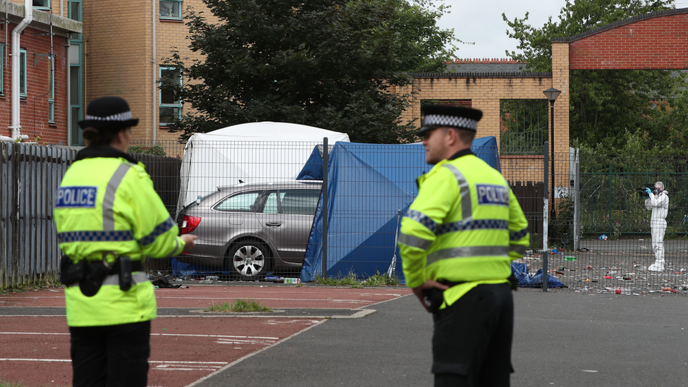 Police outside a white tent at the shooting location