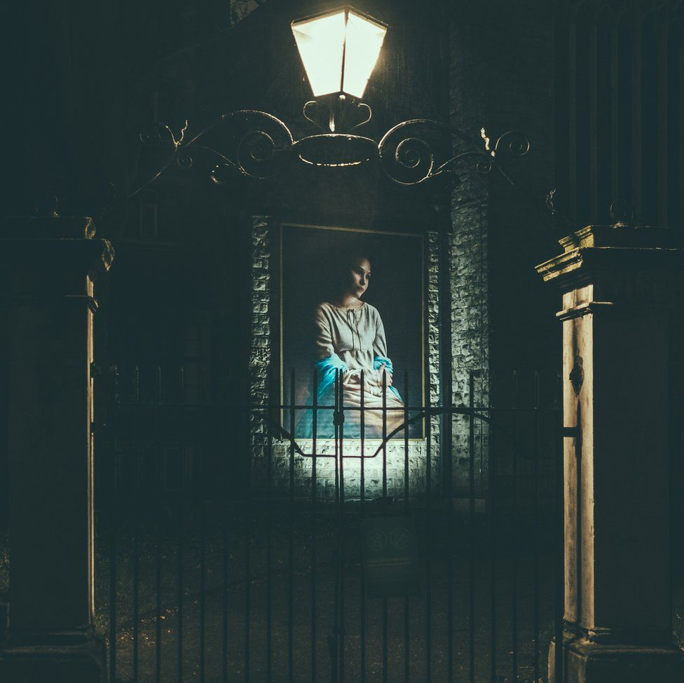 An image of a portrait of a woman looking thoughtful on a wall behind a gate