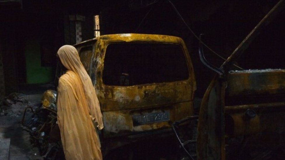 A Muslim woman looks at a burnt vehicle