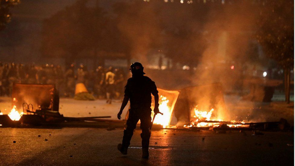 A riot police officer walks near burning fire during protests in Beirut