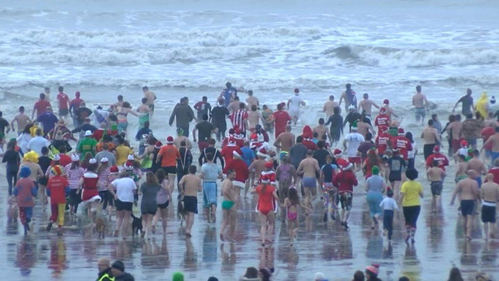 Hundreds of people run into the sea