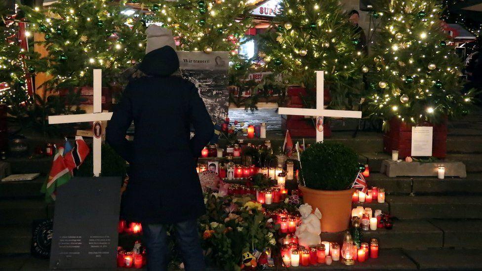 A woman watches a memorial at a Christmas market on Breitscheidplatz square