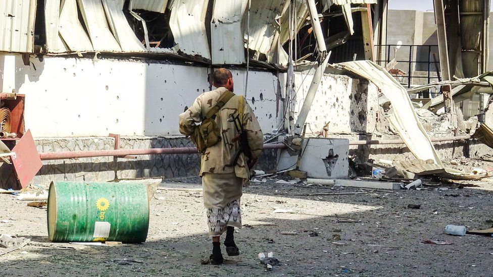A member of the Yemeni pro-government military walks through an industrial district in the eastern outskirts of the port city of Hudaydah, 18 November 2018