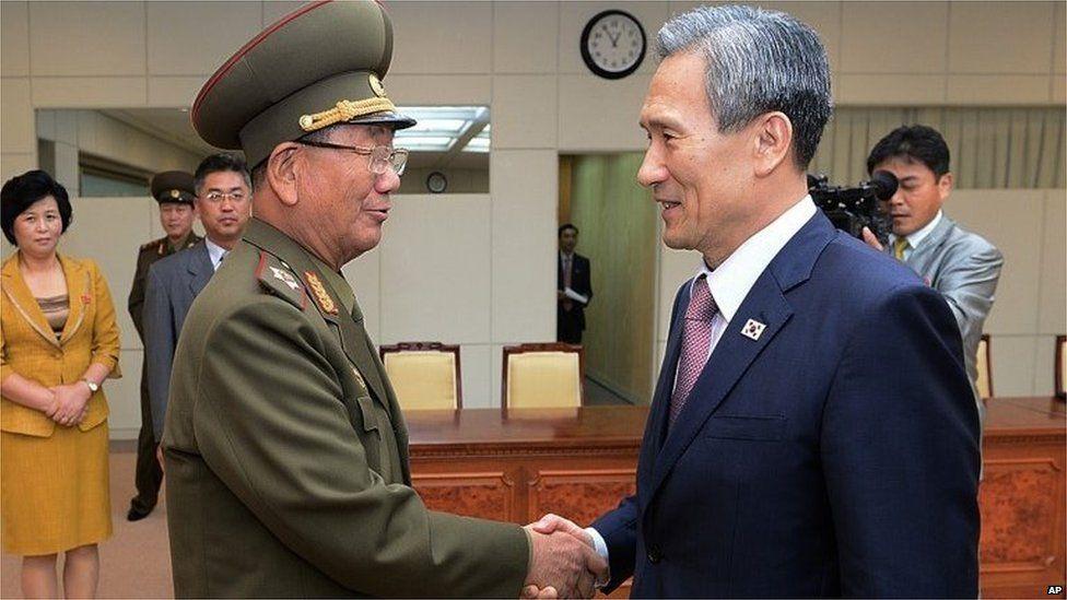 South Korean presidential security adviser Kim Kwan-jin (R) shakes hands with senior North Korean official Hwang Pyong So in Panmunjom (25 Aug 2015)