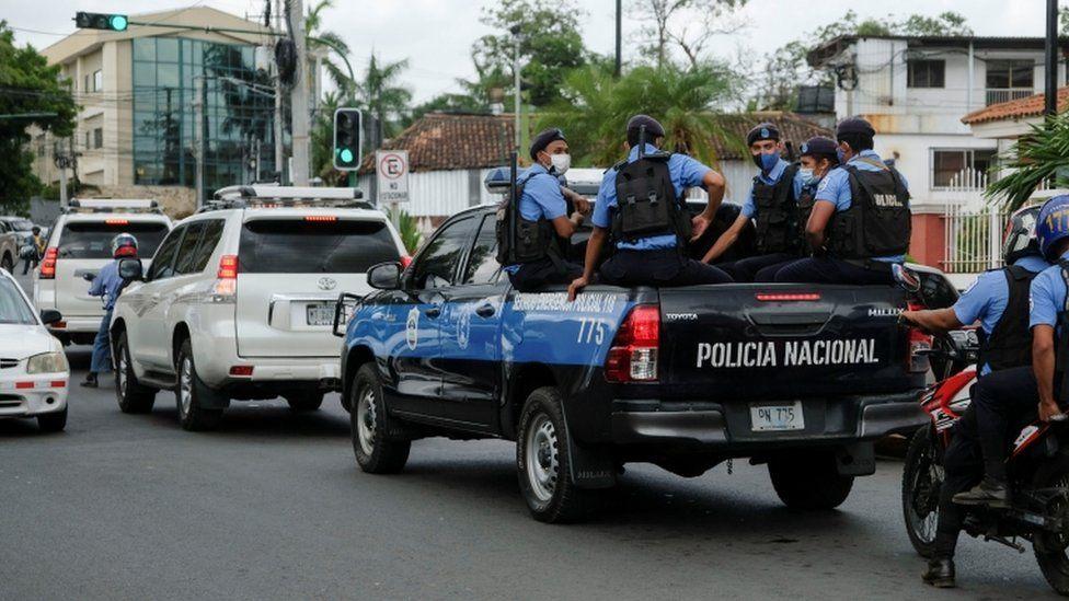 Police officers escort the vehicle of Felix Maradiaga in Managua