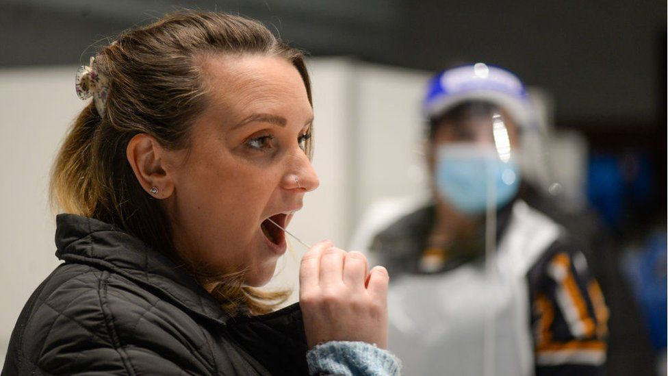 A woman takes a coronavirus test