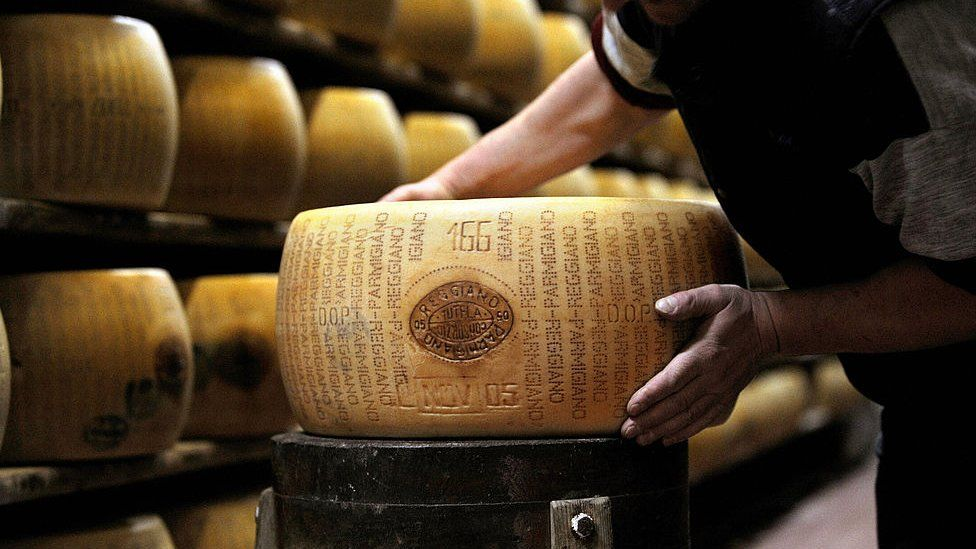 A picture taken on February 15, 2008 shows a worker checking a wheel of seasoned Parmigiano Reggiano cheese in a factory in Valestra, near Reggio Emilia