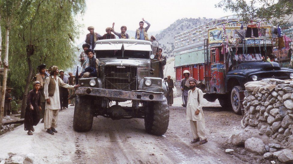Men seen in and around a large jeep in Afghanistan