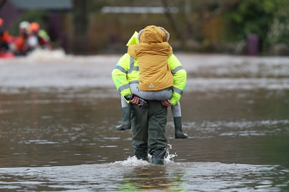 A man carries a child through floodwater in the village of Whitchurch in Herefordshire
