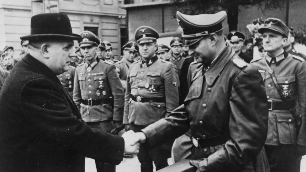 President of Slovakia Jozef Tiso (left) shaking hands with the SS's Hermann Hoefle as he presents him with an award for aiding the fight against Bolshevism, Germany, November 8th 1944.