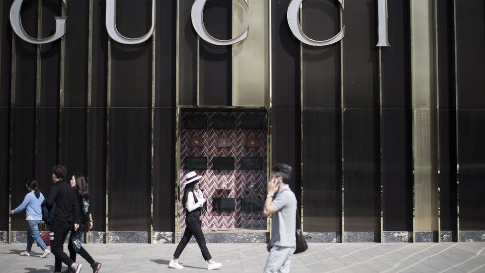 People walk next to a store of Italian luxury brand Gucci on the fourth ring road in Beijing