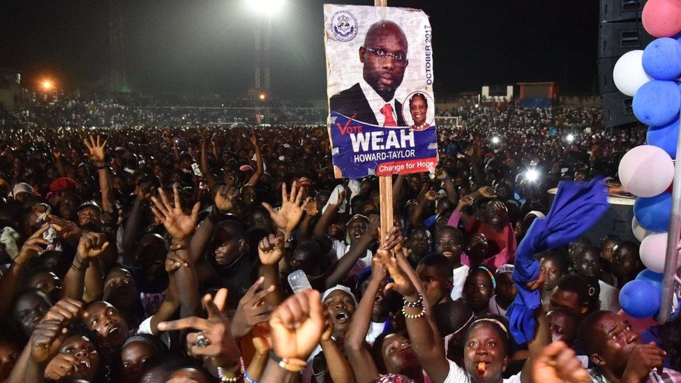 Supporters of former international Liberian football star turned politician George Weah wave during a presidential campaign rally in Monrovia on October 6, 2017