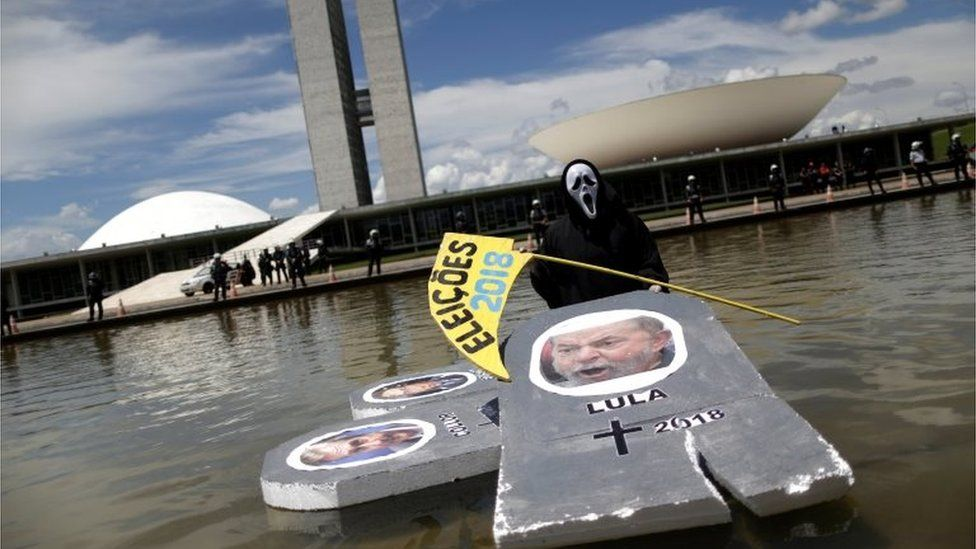 """A protester wearing a mask is seen with an image of Brazil""""s former president Luiz Inacio Lula da Silva, in front of National Congress during protest against corruption, in Brasilia, Brazil March 26, 2017."""