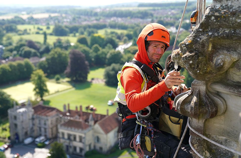 A conservator abseils down the East face of Salisbury Cathedral's Tower