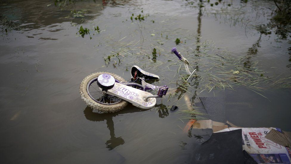 A child's bicycle floating in flood water