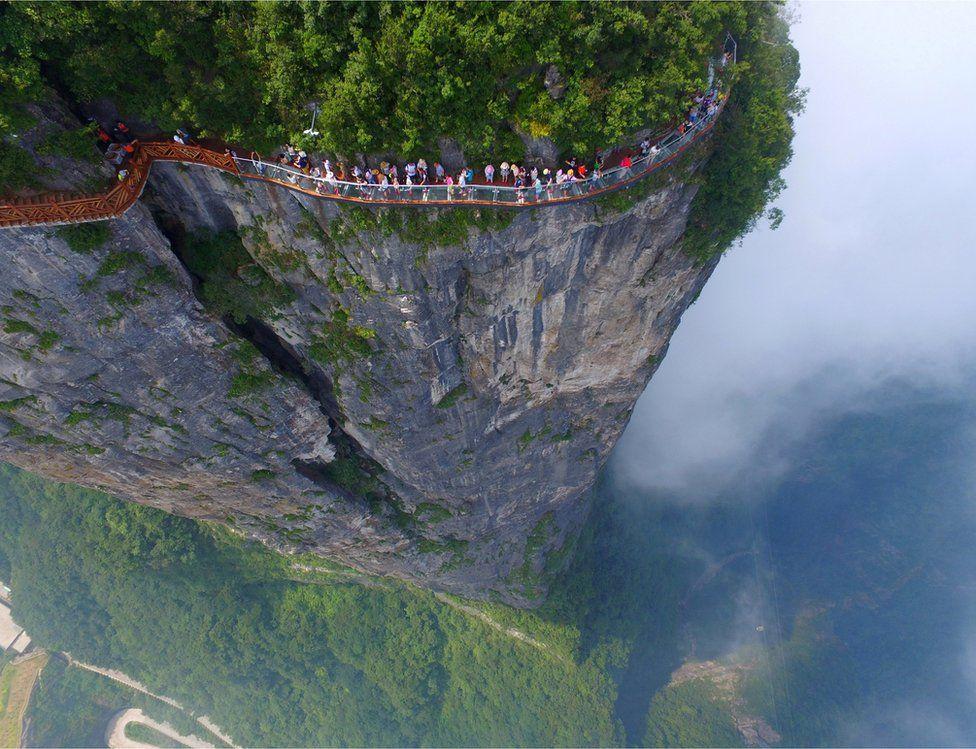 People walk on a sightseeing platform in Zhangjiajie, Hunan Province, China, 1 August 2016.