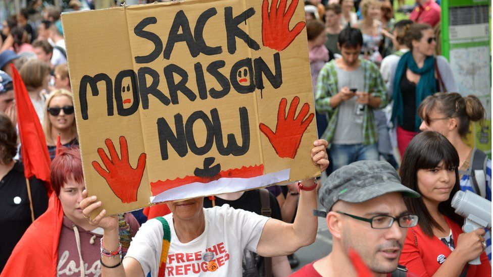 Protester holds up 'Sack Morrison Now' poster in refugee rally in Melbourne in 2013