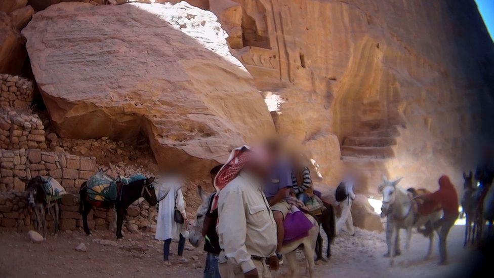 Tourists riding donkeys at Petra, Jordan