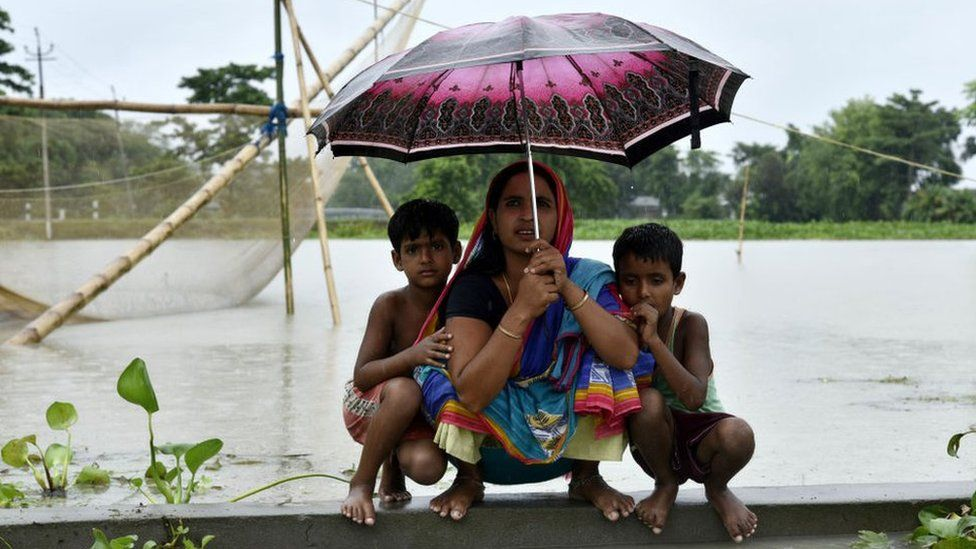 Woman and children take shelter on a height in the flood effected Kalgachia of Barpeta district of Assam, India on July 12, 2019.