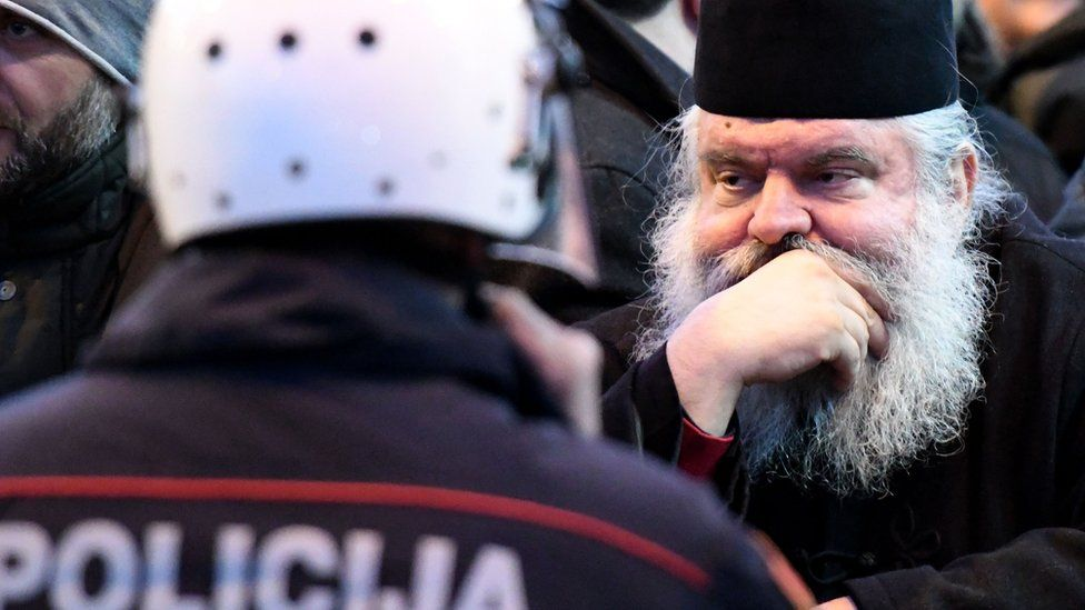 Serbian Orthodox Church clergy and believers stand in front of police near the parliament on 26 December