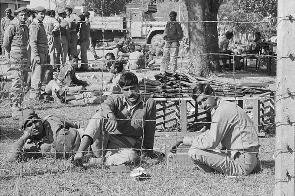 Captured Pakistani soldiers sit behind a barbed wire fence at a prison camp here.