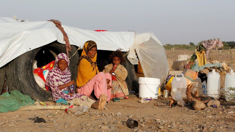 A woman and her daughters sit next to their hut at a makeshift camp for internally displaced people south of the Red Sea port city of Hudaydah, Yemen February 22, 2017