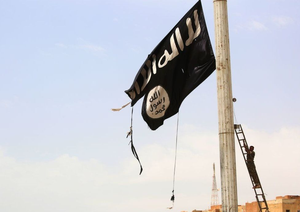A member of the US-backed Syrian Democratic Forces (SDF) removes an Islamic State group flag in the town of Tabqa on April 30, 2017