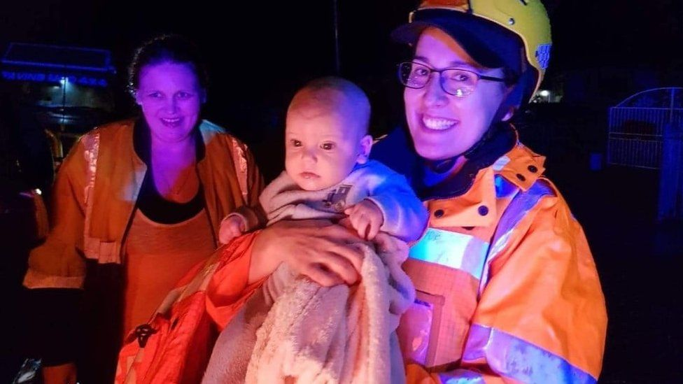 Emergency service worker holds up a baby rescued during Sydney floods