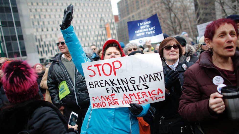"""A woman holds a sign saying """"stop breaking apart families - make America kind for the first time"""""""