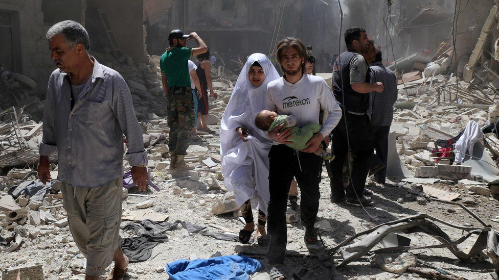 Syrian family amid rubble of destroyed buildings in Aleppo on April 28, 2016