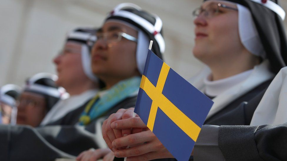 A nun holds a Swedish flag as she attends as Pope Francis arrives to lead the mass for the canonization of Swedish nun Sister Maria Elisabeth Hesselblad - 5 June 2016
