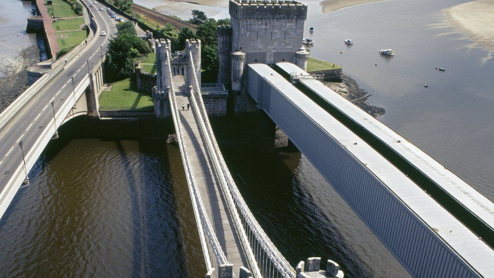 Aerial photo showing three bridges across the muddy coloured River Conwy - the road bridge is the one on the left