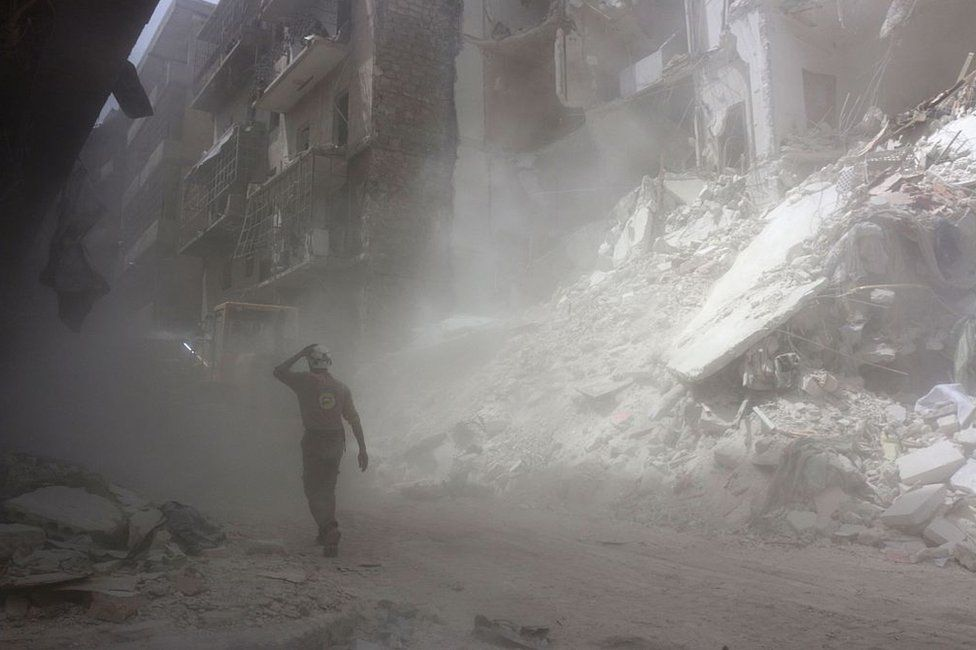 A White Helmet walks past the remains of a blasted building in Aleppo (2016)