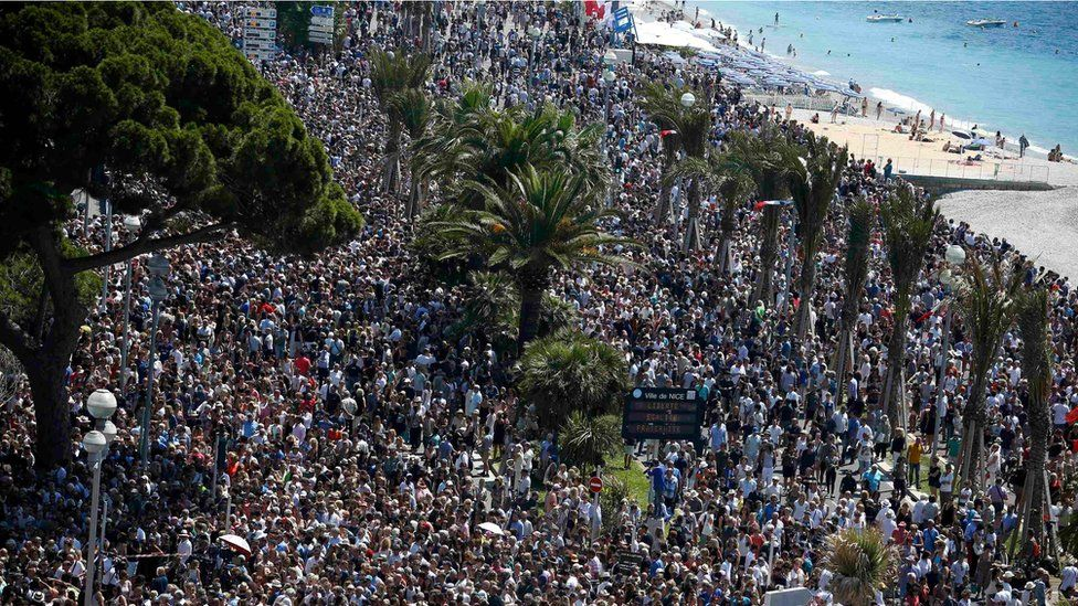 crowd gathering near a makeshift memorial on the Promenade des Anglais