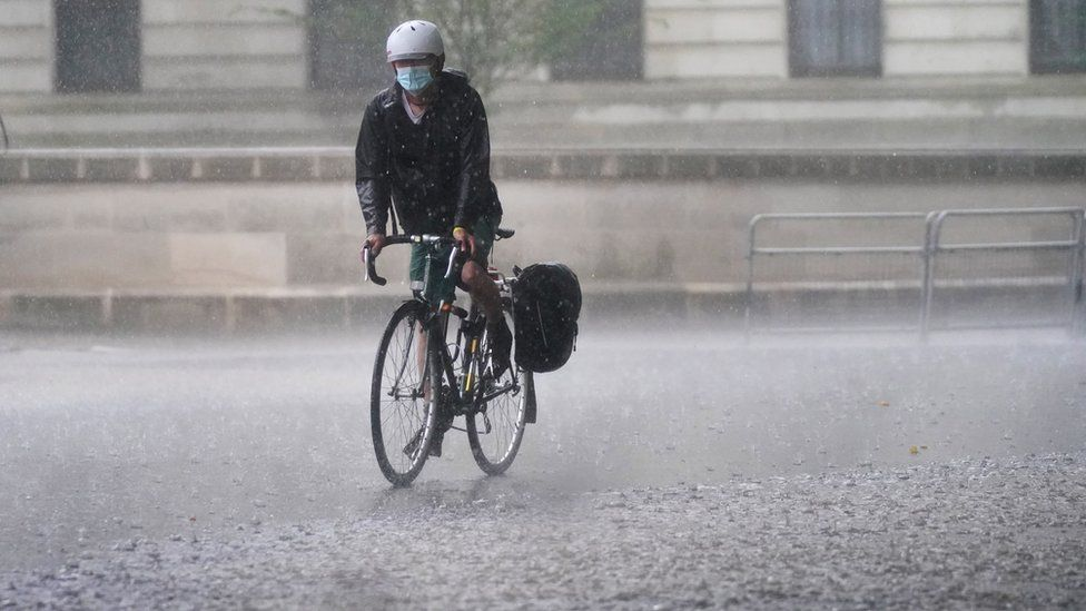 A cyclist rides through flood water in Horse Guards Road in central London
