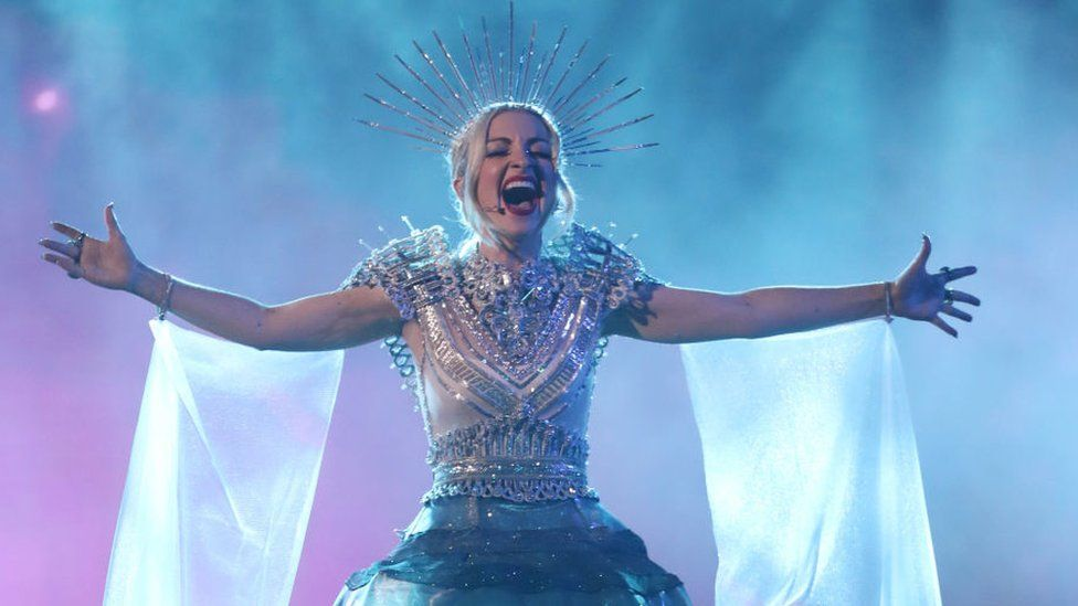 A singer with an elaborate wired headpiece and floaty material coming from her arms sings out with her arms outstretched