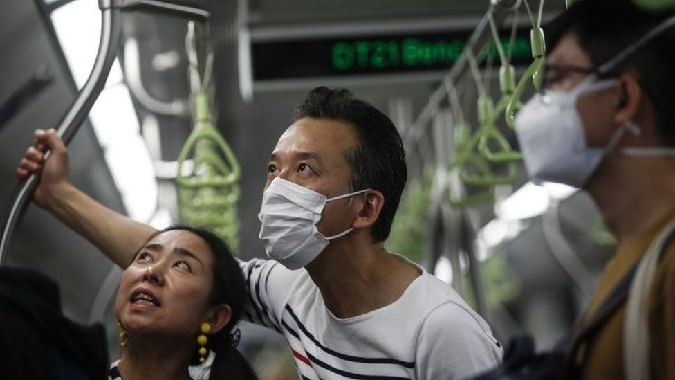 A man wearing a protective mask (C) rides the train in Singapore